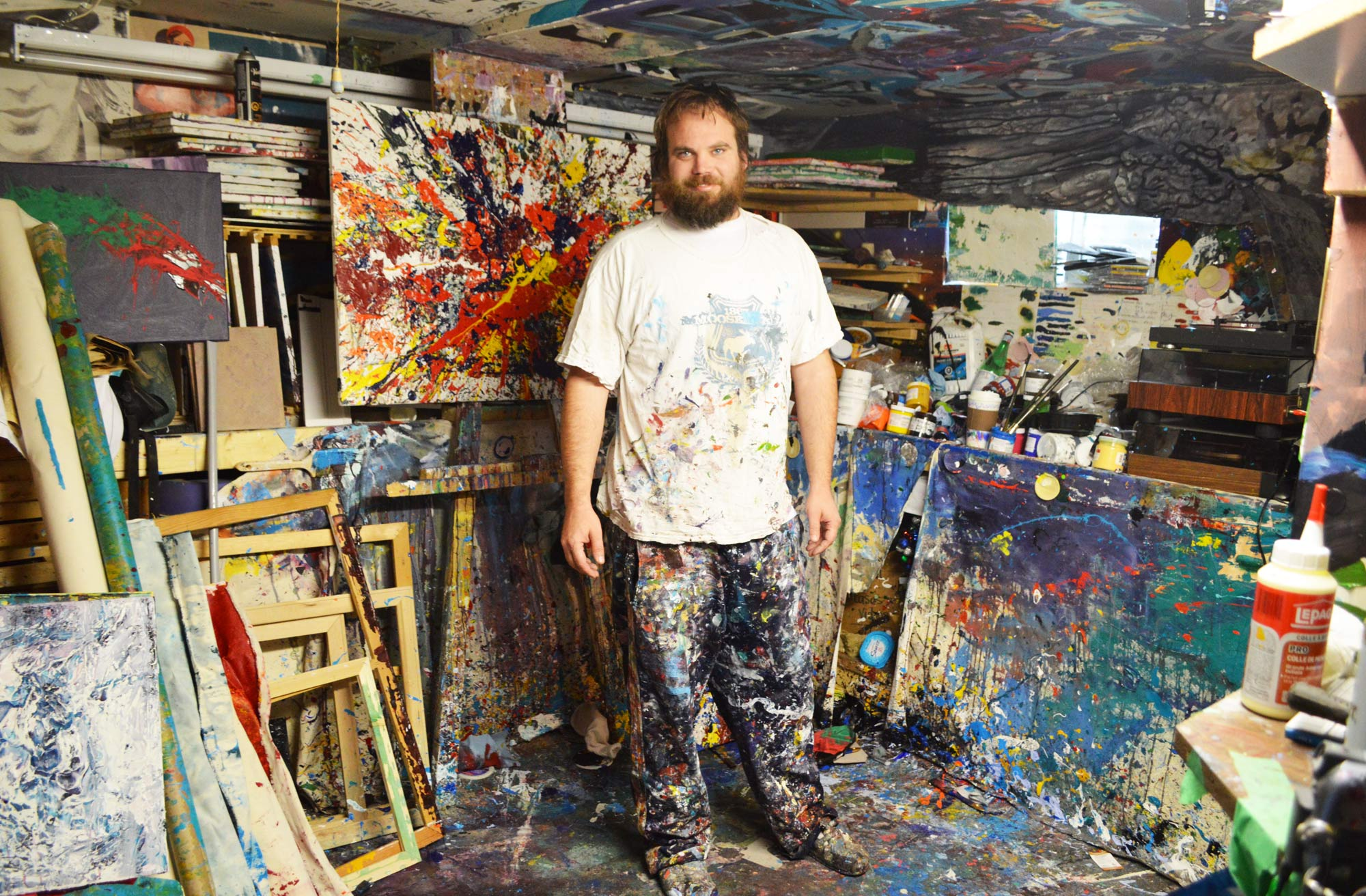 Local artist Jason Kuehnen standing in his basement studio where his creativity is unleashed.