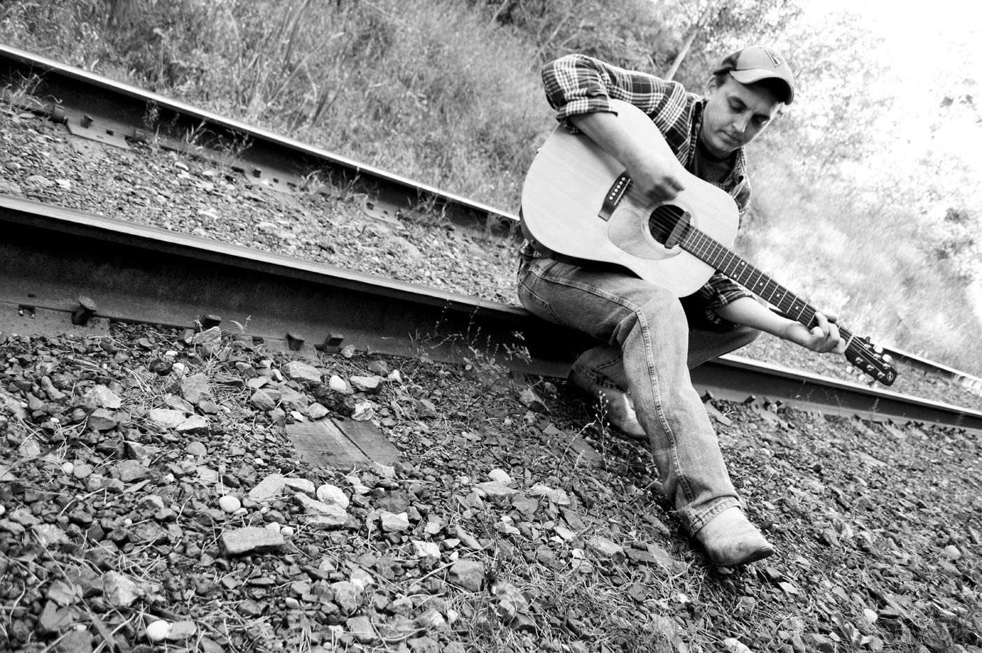 Playing an old-time country tune down at the tracks.