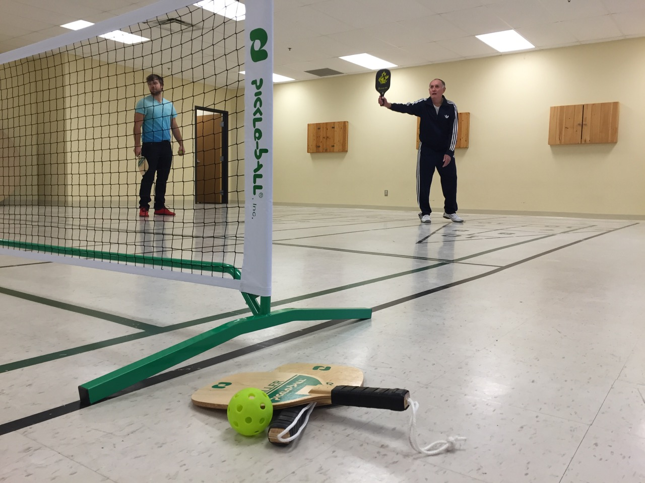 Dennis Wilks, right, shows Ben Robitaille the Pickleball basics