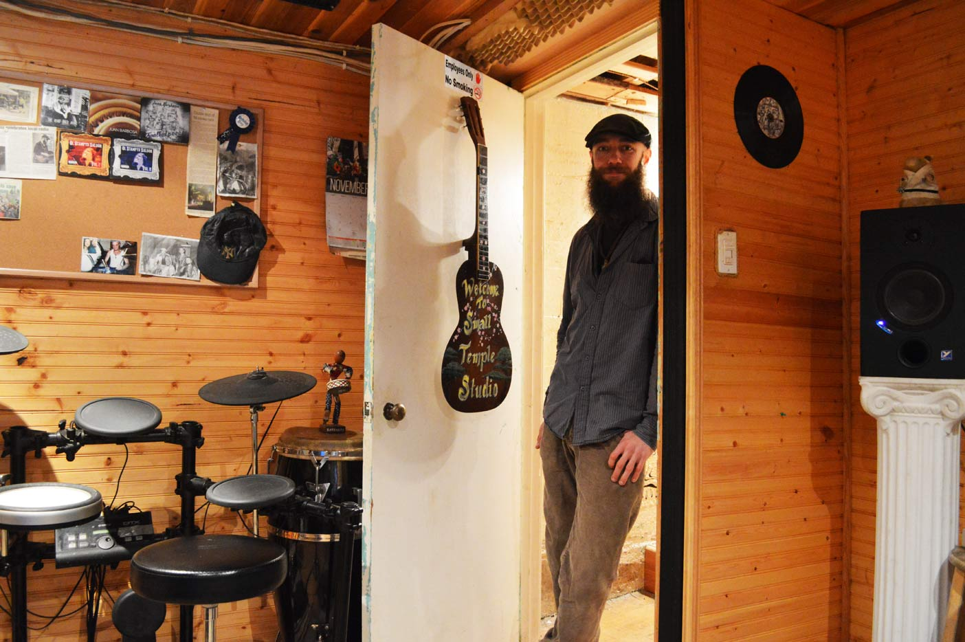 Barbosa leaning in the doorway of his studio, appropriately called Small Temple Studio. His mom made him the door sign from an old guitar he found.