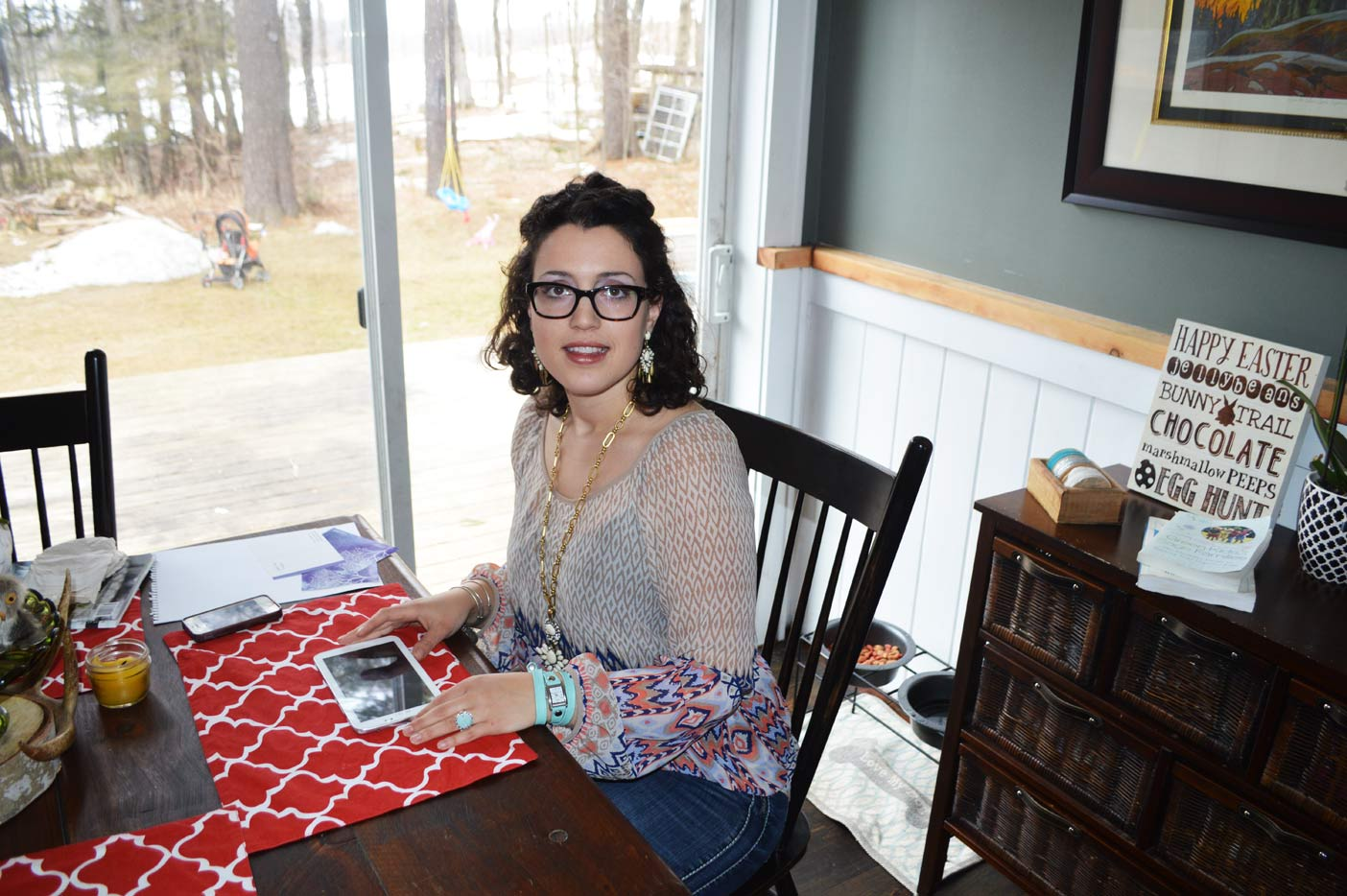 Kelly Mattice at her kitchen table with her tablet, which she uses daily for posting on her Facebook page Health Mama Muskoka.