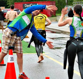 TriMuskokan co-director Rich Trenholm high-fives swimmers on their way into the transition area
