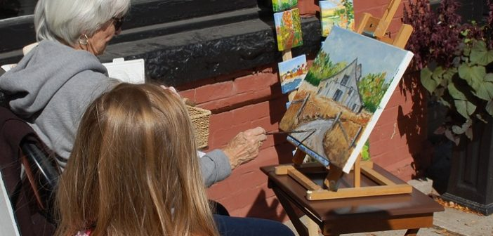 Artist Connie Kelso paints while a young passerby looks on