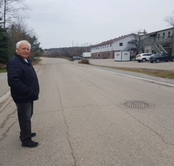 Bob Masterson stands in front of the manhole cover on Szawlowski Drive from where there was sewage flooding the road on October 28.