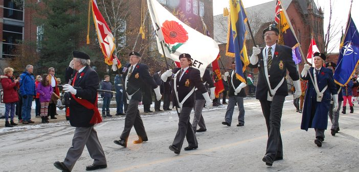 The veterans' parade, led by the Legion's Colour Guard, passes Town Hall