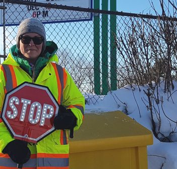 Crossing guard Amber Harrison shows off one of the new LED stop signs