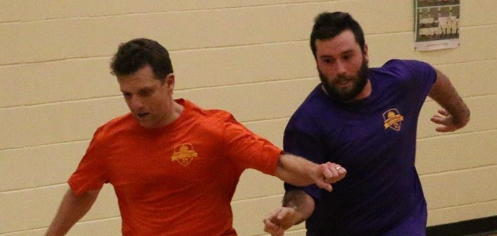 Ted Maduri of Orange Crush fights off Paul Borbeau of Crushed Grapes during Huntsville Indoor Soccer League action on Monday, Dec. 18 at Huntsville High School (supplied photo)