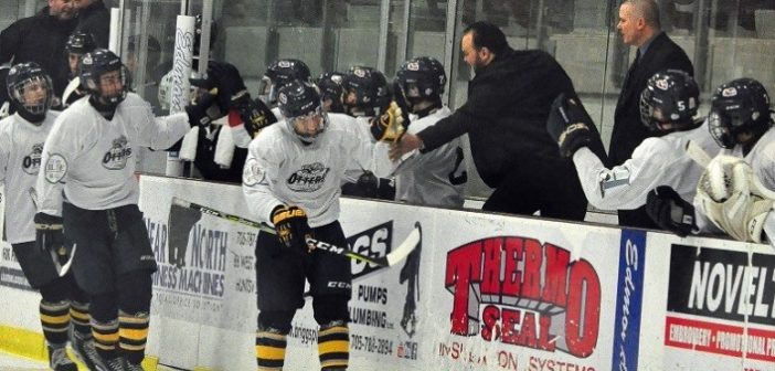 Alex Brisson gets a high five from coach Brent Tomlinson after his first goal as an Otter