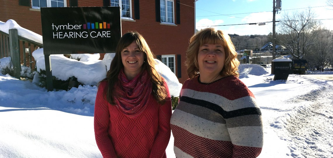 Andrea Fisher, owner, and receptionist Tina Schnurr in front of the Tymber Hearing Care office on Elm Street
