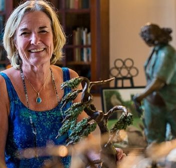 Brenda Wainman Goulet with one of her white pine sculptures (Image: artistsofthelimberlost.ca)