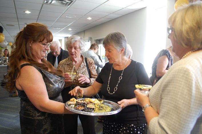 Karen Raaflaub (left) serves up tasty hors d'oeuvres to volunteers