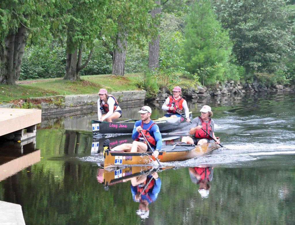 Eventual first place teams #wepaddletogether (Sprint), back, and Brace or Bust (Classic) paddle hard to the portage at the Brunel Locks Photo Cheyenne Wood