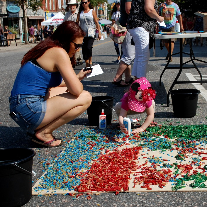Juliette Sewell adds to the macaroni street art while Holly Sewell watches