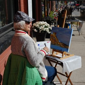 Connie Kelso enjoys a sunny painting spot in front of The Hudson