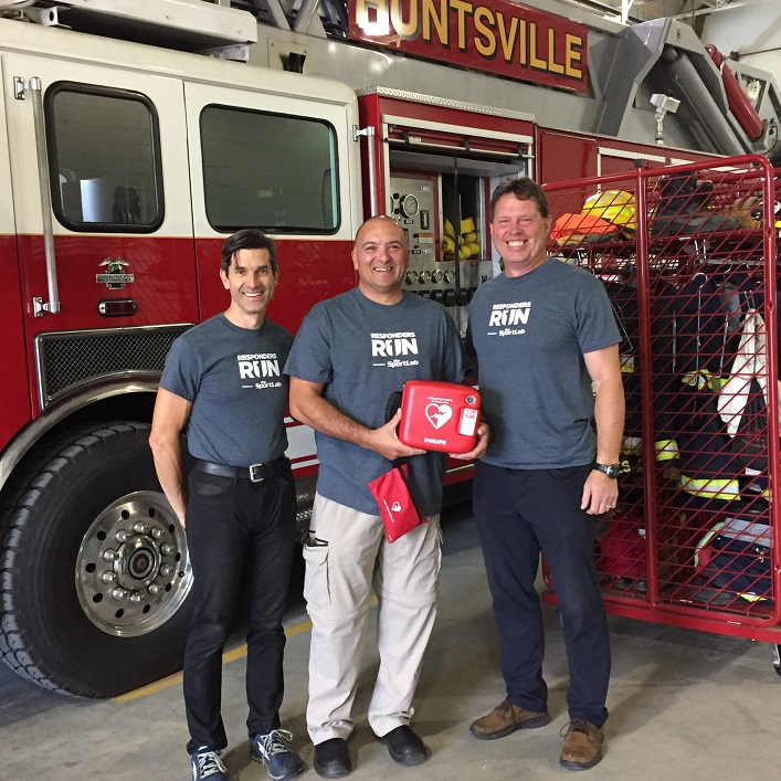 Dr. Lowell Grieb of The SportLab (left) and Roger Hennig of Save Station (right) present Huntsville firefighter Paul Calleja with an automated external defibrillator (Photo: The SportLab)