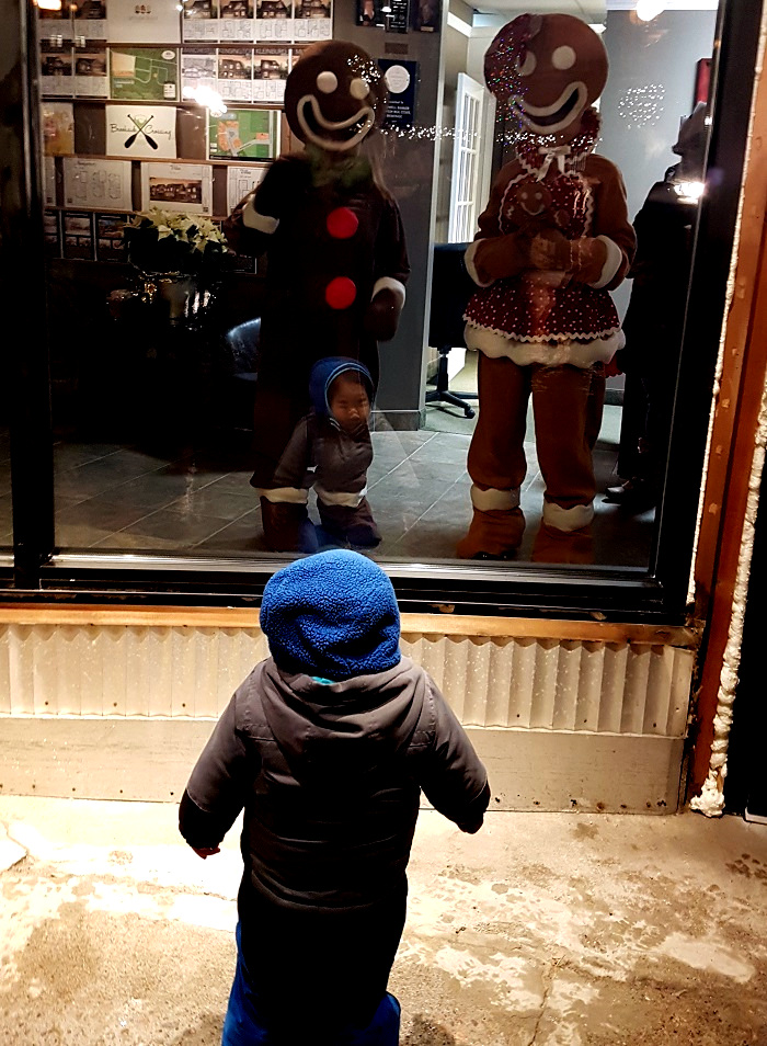 Young Everett Yang, 2, was enthralled by the gingerbread people in the Coldwell Banker Thompson window prior to the parade