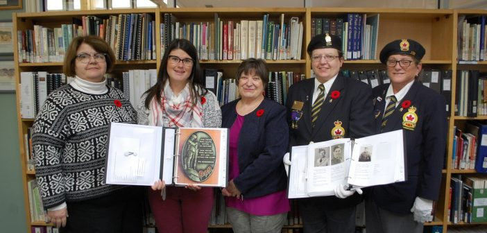 Carol Stevens (centre) presents binders filled with local WWII veterans to the Legion and Huntsville Public Library