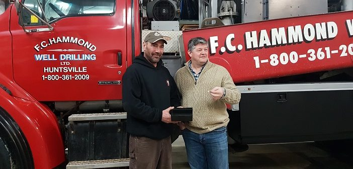 Jeff Yearley (left) and Mayor Scott Aitchison draw the lucky winner in the annual F.C. Hammond well draw