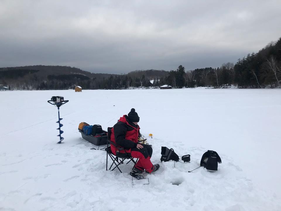 Sara Storozuk monitors the ice fishing equipment. Cedar Grove Lodge is in the background. (Photo courtesy of Sara and Daniel Storozuk)