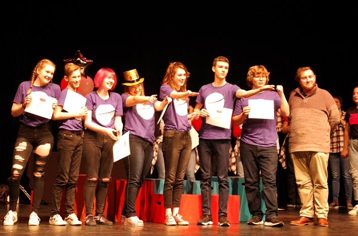 HHS Startdust (from left) Sarah-Emily Waller, Jacob Hunter, Megan Maynard, Aria Platts-Boyle, Emma Flaxman, Oliver Byl, and Max Hill receive their third-place certificates from Canadian Improv Games judge A.J. Comeau (right)