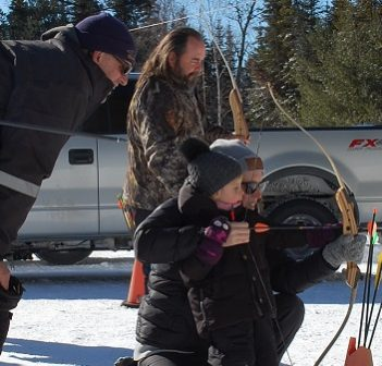 Izzy (foreground) and Jenny Smith try their hand at archery at the 49th annual Dwight Winter Carnival