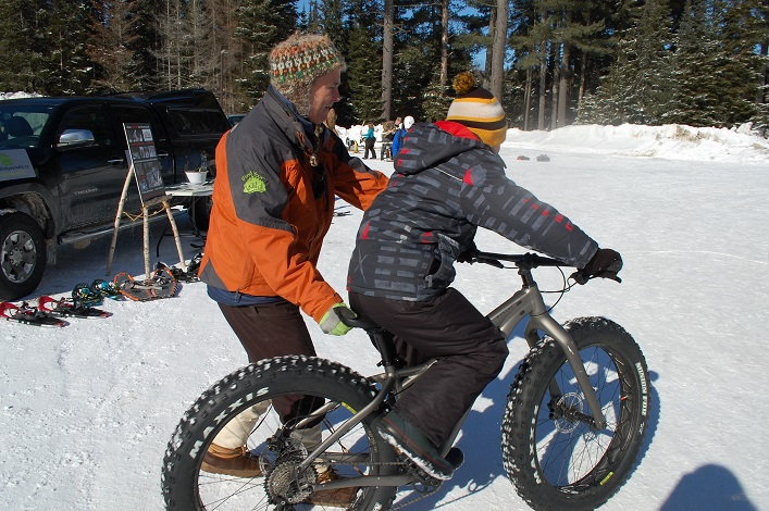 Jamie Honderich aka Hondo of Find Your Wild helps a young rider get started on a fatbike provided by Algonquin Outfitters