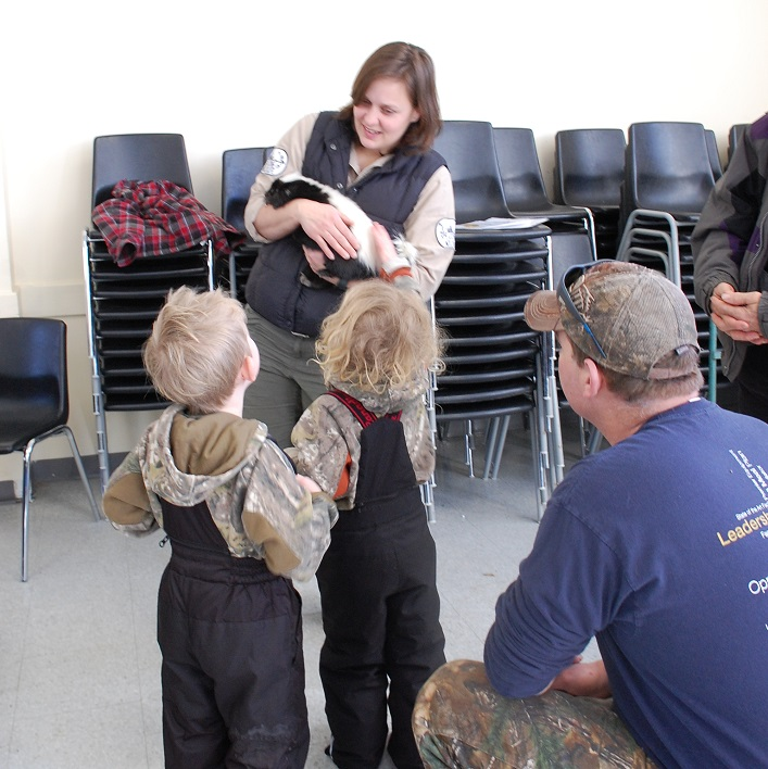 Krystal Hewitt with Speaking of wildlife holds Chanel the skunk so Winter Holtby can give her a pat while Finn (left) and Fred Holtby wait their turn