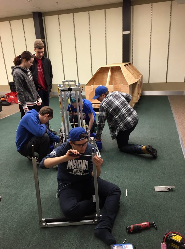 Team members prepare the robot for action in the practice space. Pictured are Keira Brisebois and Oliver Byl (standing), Sam Topps, Morghan Kiverago, and Jeff Waller (around the robot, left to right), and Andrea Bonafini (foreground).