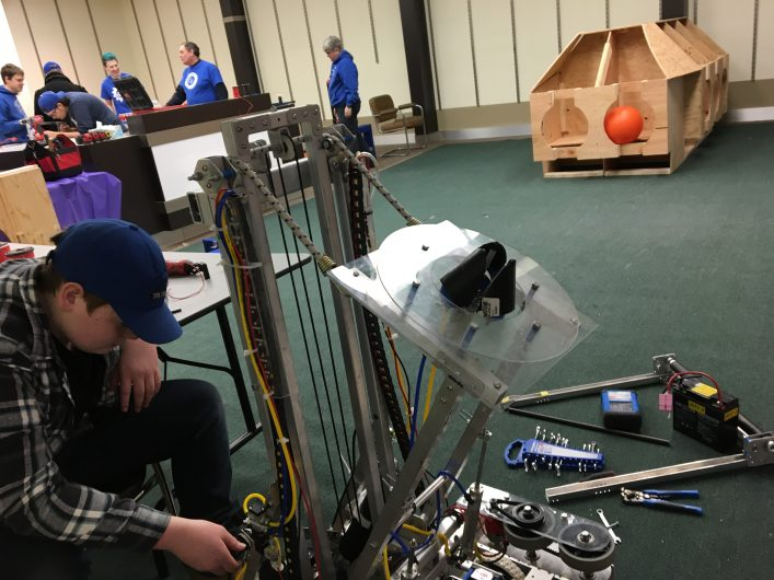 Jeff Waller works on the team's robot. In the background are one of the field elements, the cargo ship, on the right and other team members and mentors on the left.