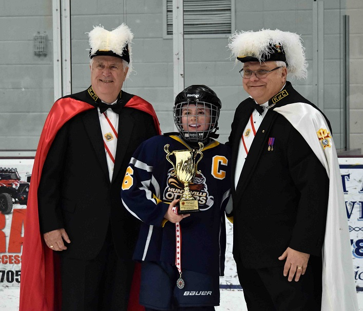 Team captain Hunter Stillar accepts the silver cup from members of the Knights of Columbus