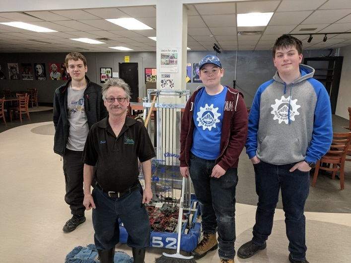 Members of the Hoya Robotics team and their robot help Bradley Brandt with some sweeping on his last shift (Photo: @hhs4152 / Twitter)
