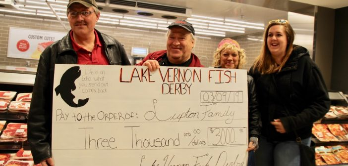 (From left) Barry Groomes presents a cheque to Bob Lupton, while Tammie Lupton, and Shelbie Groomes do the heavy lifting