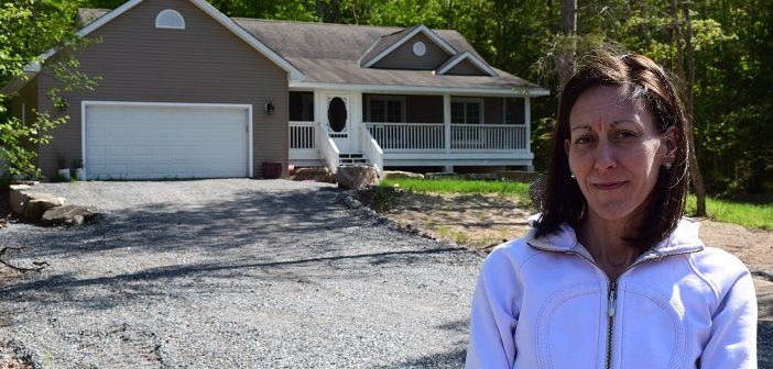 Bridget Austin in front of the home her family bought, not knowing it was toxic