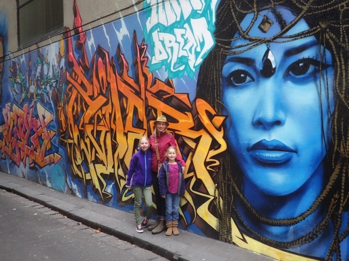 (From left) Joan, Mara and Ellie in front of some Melbourne street art (supplied)