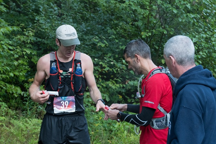 Kip Arlidge re-fueling at an aid station with Dr. Lowell Grieb during the 2019 Haliburton Forest Trail Race (Photo: David Sweeney)
