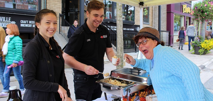 Jennifer Jerrett samples Huntsville Brewhouse's mac n cheese with Hilda Chan and Luke Murphy