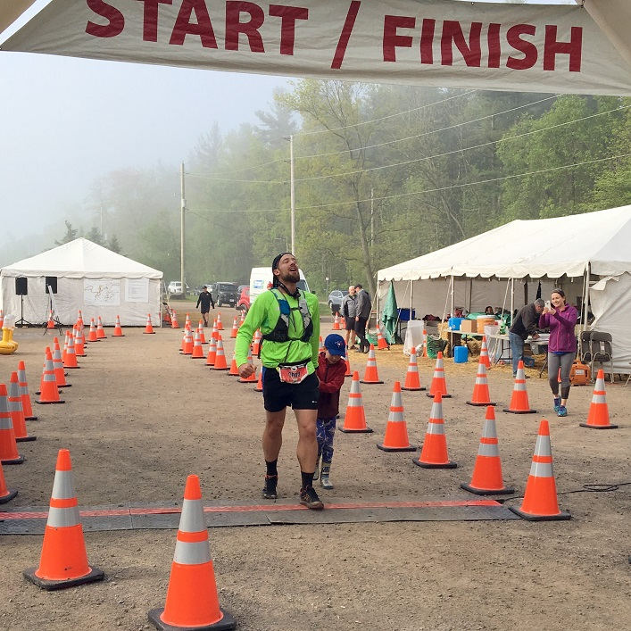 Chad finishing his first 100-mile race with his son at his side (Courtesy of Chad Barber)