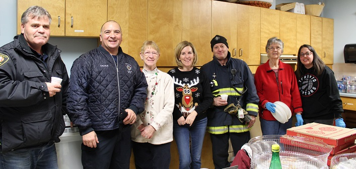 Kitchen volunteers (pictured with some local firefighters) provide sustenance to those collecting and sorting donations. (From left) fire chief Steve Hernen, training/suppression captain Paul Calleja, Jan Harres, Jodi Madden, deputy fire chief Gary Monahan, Janis Schut, and Shirley Gibson. Harres has been making and serving hot chocolate for food drive volunteers for 29 years.