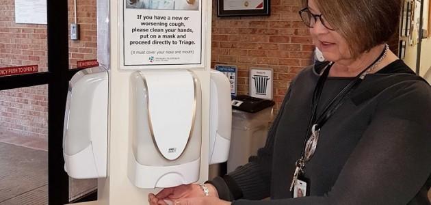 MAHC CEO Natalie Bubela uses the hand sanitizing station at Huntsville Hospital (supplied)