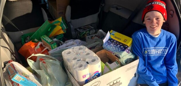 Rowan Simpson,13, with donations he collected for The Table food bank (supplied)