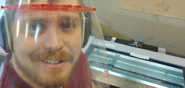 Thomas Morton with the laser cutter used to cut components for the face shields (supplied)